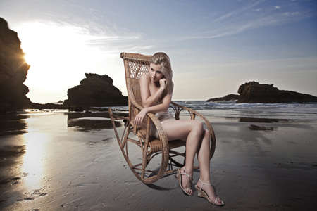 rocking chair: blonde beauty sitting on a rocking chair on the beach  Stock Photo