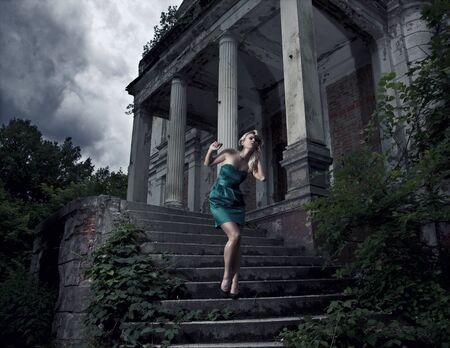 beautiful blonde woman posing near the dark castle