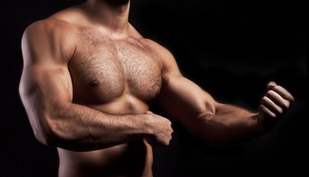 human chest: strong athletic man isolated on black background