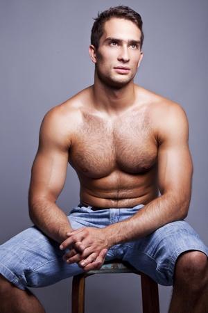 chest hair: muscular man sitting on a chair