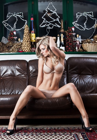 beautiful blonde woman posing on coach  Stock Photo