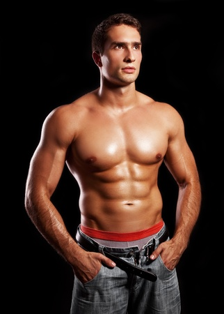 handsome powerful muscular man isolated on black  photo