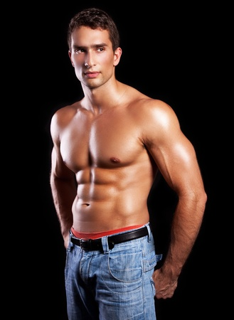 muscular male: young muscular man isolated on black background