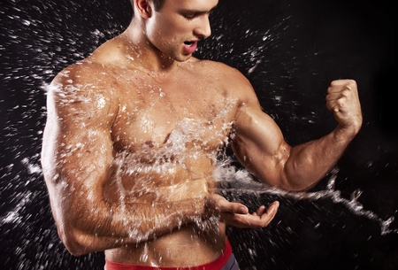 muscular male: muscular man having shower