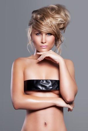 Belle femme blonde avec coiffure de mode sur le fond gris Banque d'images