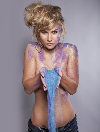 beautiful blonde woman with colorful makeup pouring a blue sand