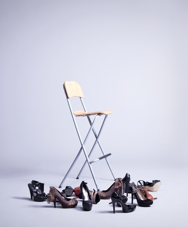 chair on gray background with many shoes  photo