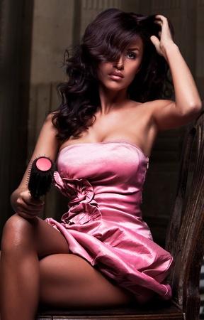 barbershop: Prachtige brunette schoonheid zit op een stoel in roze jurk Stockfoto