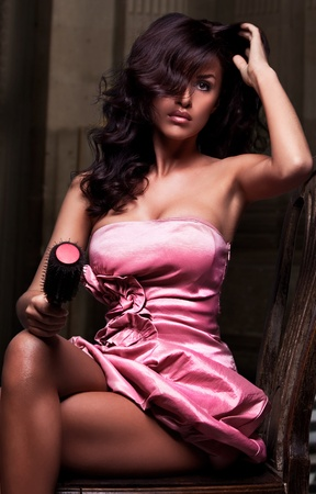 Stunning brunette beauty sitting on a chair in pink dress