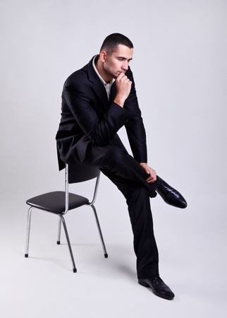 Elegant young businessman sitting on a chair and thinking over gray background  photo