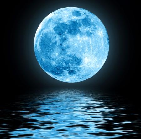 Volle blauwe maan over het water met reflecties