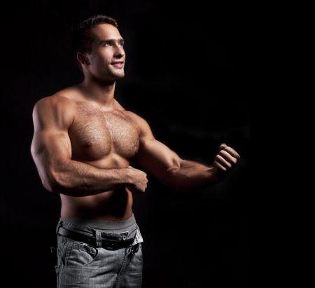 strong light: muscular man posing on a black background
