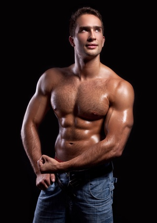 pectoral muscle: handsome powerful muscular man isolated on black