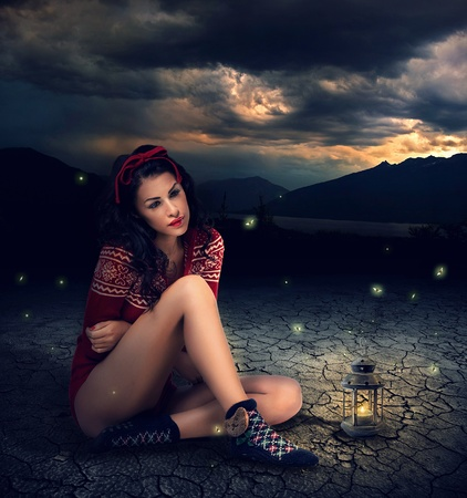 fashion story: Fantasy style photo of a young beauty brunette woman with Candle Lamp  Stock Photo