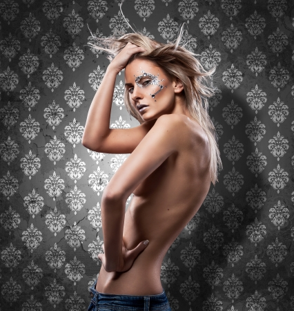 beautiful blond woman whit diamonds posing on wall  photo