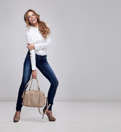 Beautiful happy woman holding a bag Stock Photo - 13838262