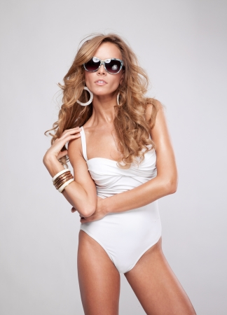 Young sexy woman with sunglasses on grey background photo