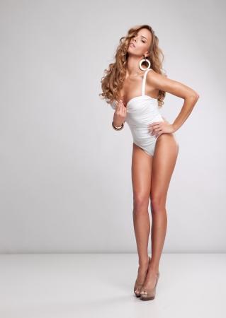 Jeune femme sexy sur fond gris Banque d'images