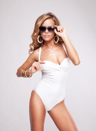 Femme sexy dans le maillot de bain avec des lunettes de soleil