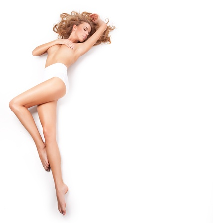 Delicate blond woman lying on a white background photo