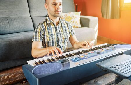 A man learning to play the piano while watching an online course at home