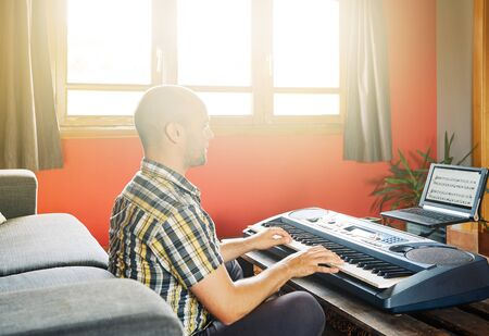 Man playing piano while taking online lessons