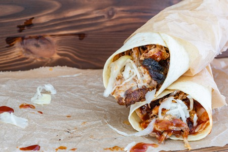 Pulled Pork Wraps with hot BBQ sauce on a wooden tabel Imagens
