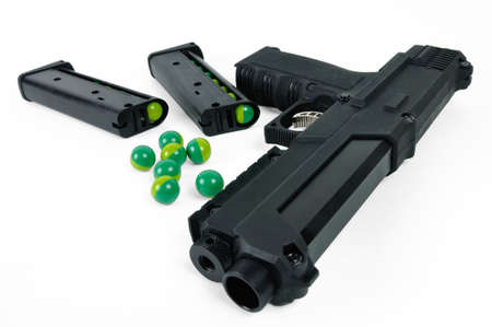 dispersed: paintball gun with two magazines and balls dispersed on a white background