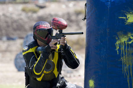 Paintball player shooting in the field photo