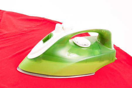 steam iron: Ironing a wrinkled red shirt with a clothes iron green and white
