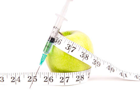 genetic food modification: Syringe with blue liquid on a green apple surrounded by a measuring tape