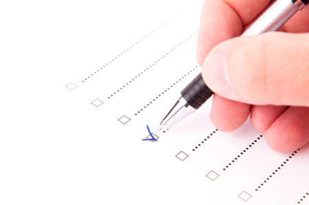 answer approve of: Hand checking a box with a yes with a pen Stock Photo