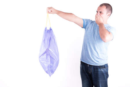 stench: Man with a stinking garbage bag in hand on white background