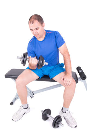 situp: Man doing exercises with dumbbells in a sit-up bench on white background
