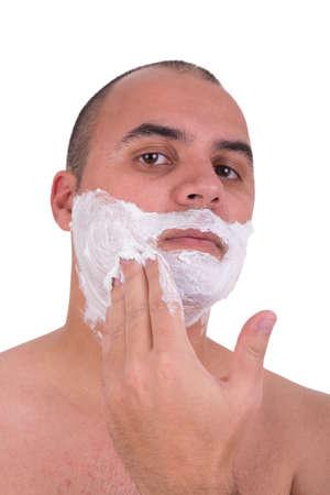 shaving cream: Man putting on shaving cream on white background