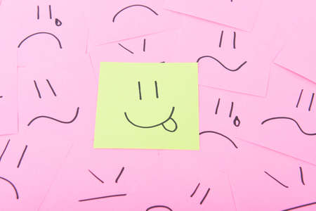 posits: Yellow post it with happy face on red posits with sad faces