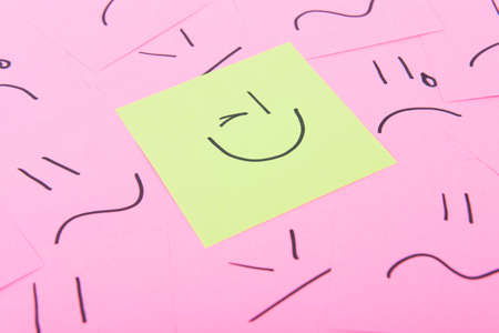 Yellow post it with happy face on red posits with sad faces