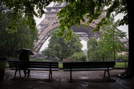 A woman sitting on the bench waiting for the rain