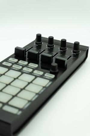 Beat machine device for electronic music composer.Techno dj play and remix musical tracks with modern drum machine with knobs and pads isolated on white background, music concept