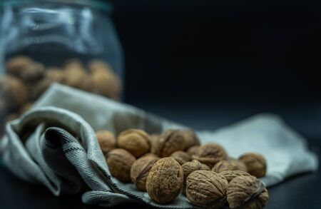 close up of a nuts on kitchen cloth, in the back a jar full of nuts, on a black background, healthy food concept.