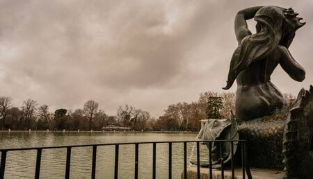 Views of the pond in Retiro Park in Madrid on a cloudy day with one of the sirens in the foreground. Travel concept.