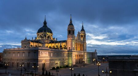 Night view of the Saint Mary the Royal of La Almudena Cathedral in Madrid on a cloudy day without people. Travel concept. Stock Photo