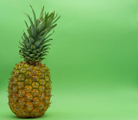 Isolated pineapple on green background on the left with space for text on the right. Healthy food concept. Tropical fruit. Reklamní fotografie - 140372155