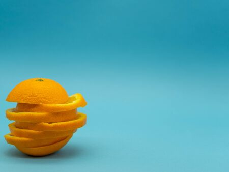 Whole orange slices mounted on top of each other on the left side of the image with space on the left for text, isolated on a blue background. Citrus fruit. Healthy food concept. Reklamní fotografie - 140373815