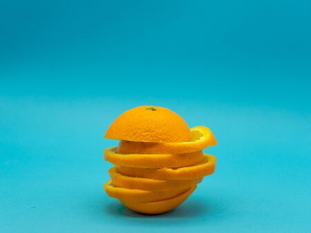 Whole orange slices mounted on top of each other in the center of the isolated image on a blue background. Citrus fruit. Healthy food concept. Reklamní fotografie