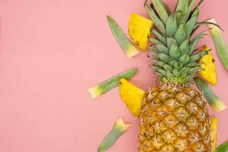 Whole pineapple with pieces and leaves around, isolated on a pink background. Space on the left. Tropical food. Healthy and ecological food concept. 免版税图像