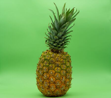 Isolated pineapple on a green background in the center of the image. Tropical fruit. Healthy food concept. Reklamní fotografie