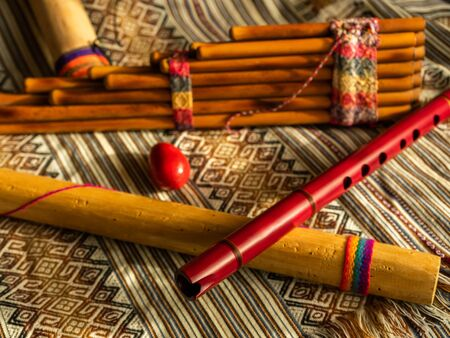 Andean instruments, zampoña, quena, rain stick, and egg shaker. On Peruvian colored poncho. Natural light. Concept of traditional instruments.