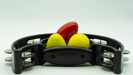 Black tambourine with eggs shakers on top on a white background with space at the top of the image. Concept percussion instruments. Banque d'images
