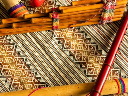 View from above of Andean instruments. Pan flute, quena, and rain stick. On Peruvian colorful poncho. Natural light. Concept of traditional instruments. Stock Photo